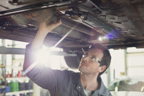Mechanic working under car in auto repair shop - CAIF08791