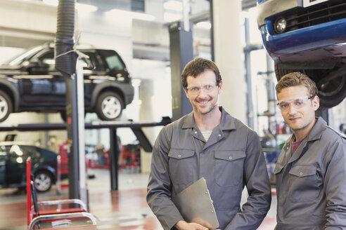 Portrait confident mechanics in auto repair shop - CAIF08800