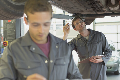 Mechanic with clipboard working under car in auto repair shop - CAIF08803