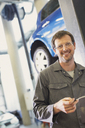 Portrait confident mechanic in auto repair shop - CAIF08806