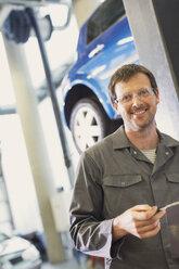 Portrait confident mechanic in auto repair shop - CAIF08806