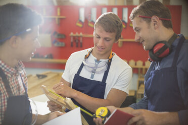 Carpenters measuring wood in workshop - CAIF08818
