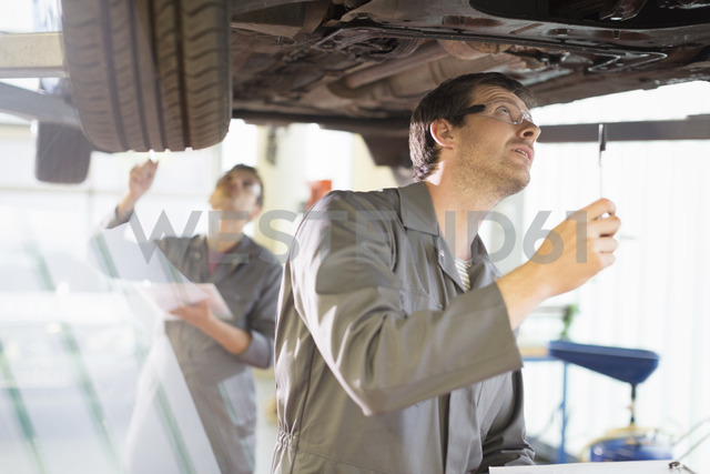 Mechanic working under car in auto repair shop - CAIF08827