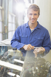 Portrait confident mechanic working on engine in auto repair shop - CAIF08836