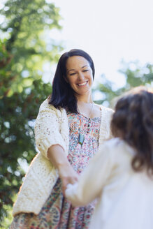 Smiling mother and daughter holding hands outdoors - CAIF08845