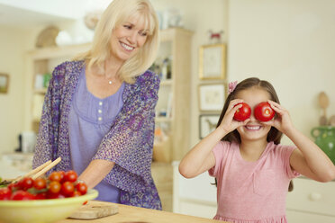 Portrait playful granddaughter covering eyes with tomatoes in kitchen - CAIF08851
