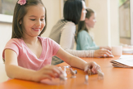 Smiling girl playing with miniature toy animals - CAIF08854
