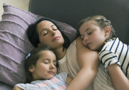 Serene mother and daughters napping on sofa - CAIF08857