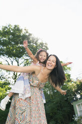 Portrait carefree mother piggybacking daughter with arms outstretched - CAIF08863