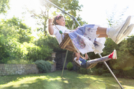 Carefree girls swinging in backyard - CAIF08869