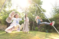 Carefree multi-generation women swinging in backyard - CAIF08872