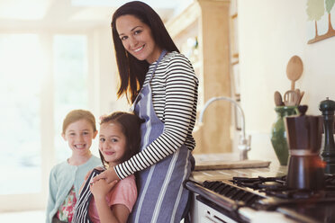 Portrait smiling mother and daughters in kitchen - CAIF08875