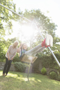 Grandmother pushing carefree granddaughter on swing in backyard - CAIF08878