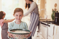 Portrait smiling girl baking holding bowl of flour in kitchen - CAIF08884