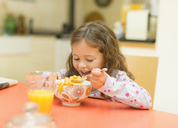 Girl eating cereal at breakfast table - CAIF08890