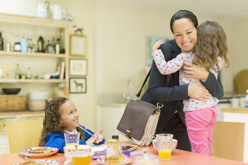 Working mother hugging daughter goodbye at breakfast table - CAIF08902