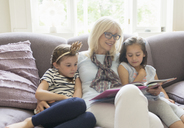 Grandmother and granddaughters reading book on living room sofa - CAIF08908
