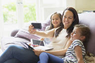 Mother and daughters taking selfie on living room sofa - CAIF08911