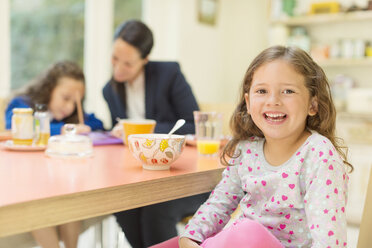 Portrait enthusiastic girl at breakfast table - CAIF08926