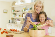 Grandmother and granddaughter tossing salad in kitchen - CAIF08938