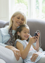 Grandmother and granddaughter sharing headphones listening to music on sofa - CAIF08941