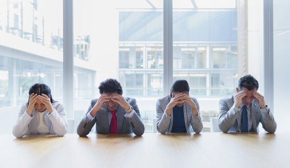 Stressed business people with heads in hands at conference table - CAIF08968
