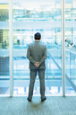 Businessman standing at atrium window with hands behind back - CAIF08992