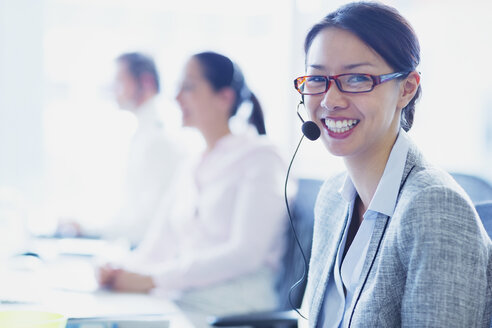 Portrait of smiling businesswoman talking on the phone with headset - CAIF09004