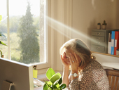 Stressed woman using computer in sunny home office - CAIF09007