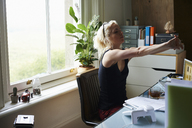 Young woman stretching arms at desk in home office - CAIF09010