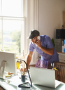 Man talking on telephone and using computer at desk in sunny home office - CAIF09013