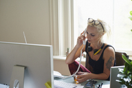 Young woman with headphones and tattoo drinking tea and talking on telephone in home office - CAIF09016