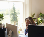 Tired woman with head in hands at computer in home office - CAIF09022