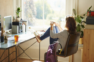 Pensive woman looking through window with feet up on desk in sunny home office - CAIF09028