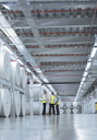 Workers in reflective clothing talking near large paper spools in printing plant - CAIF09073