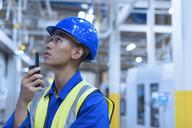 Worker in hard-hat using walkie-talkie in factory - CAIF09085
