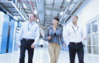 Business people walking in factory corridor - CAIF09088