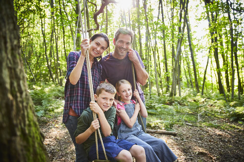 Portrait smiling family at rope swing in woods - CAIF09091
