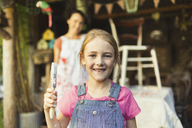 Portrait smiling girl holding paintbrush - CAIF09109