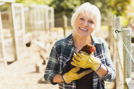 Portrait smiling woman holding chicken near coops - CAIF09112