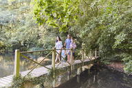 Family crossing footbridge in park with trees - CAIF09121