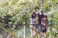 Family standing on footbridge in park with trees - CAIF09157
