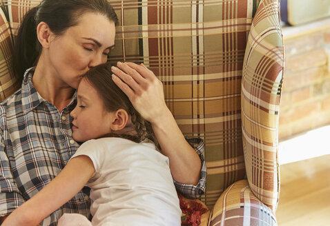 Tender mother cuddling sleeping daughter in armchair - CAIF09169