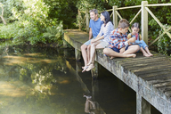 Family relaxing on footbridge over pond - CAIF09193