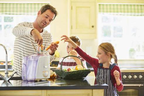 Family juicing vegetables in kitchen - CAIF09208