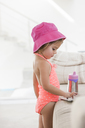 Toddler girl in bathing suit using digital tablet at sofa - CAIF09220