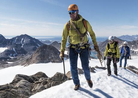 Greenland, Sermersooq, Kulusuk, Schweizerland Alps, mountaineers walking in snowy mountainscape - ALRF00950