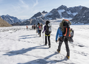 Greenland, Sermersooq, Kulusuk, Schweizerland Alps, group of people walking in snow - ALRF00953