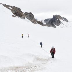 Greenland, Sermersooq, Kulusuk, Schweizerland Alps, group of people walking in snow - ALRF00956