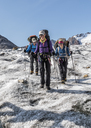 Greenland, Sermersooq, Kulusuk, Schweizerland Alps, three smiling people walking in snowy mountainscape - ALRF00983